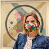 Kandinsky Circles in a Circle Face Mask worn by a model in front of the painting