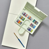 Cotman Compact Watercolor Set, open, with a pad and paintbrush