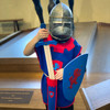 Child in helmet and tabard with sword.