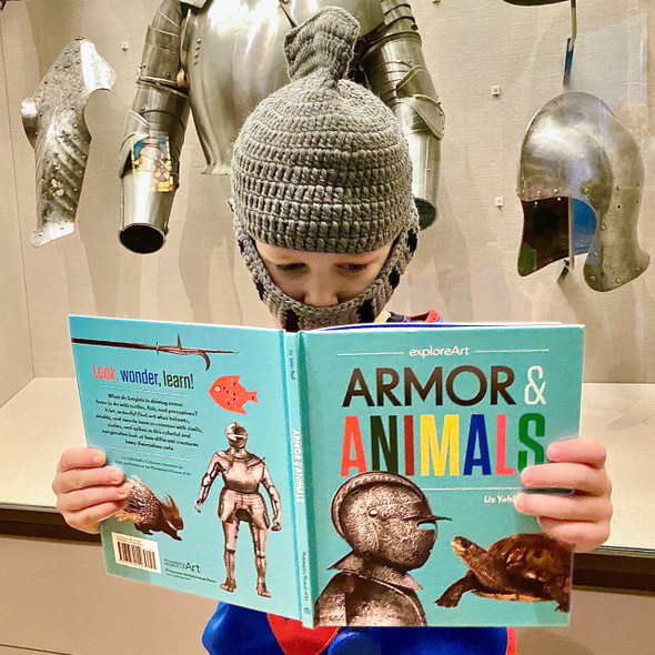 Knitted Knight Helmet Hat being worn by boy reading Amor and Animals book