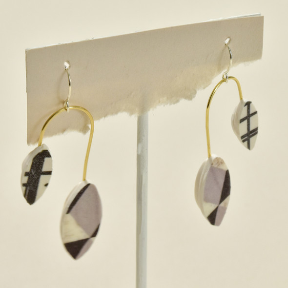 Balanced Leaves Polymer Earrings Black & White, hanging on stand