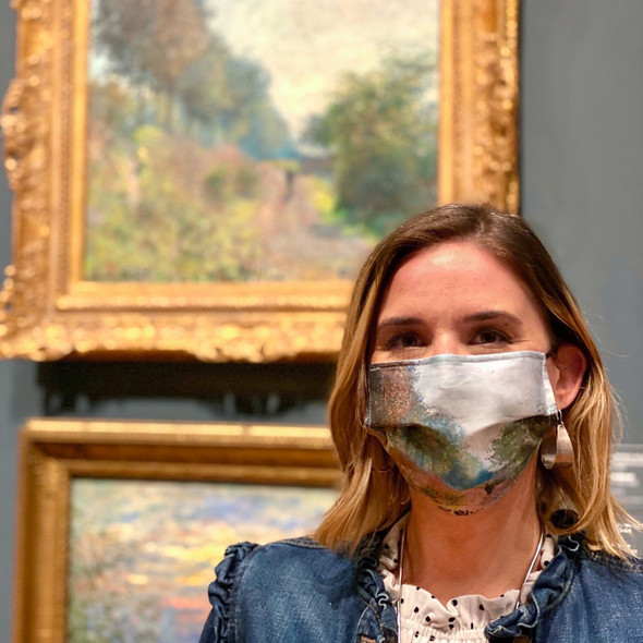 Monet Sheltered Path Face Mask by Ana Thorne being worn by a woman standing in front of Monet painting
