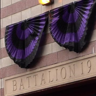 Purple and black funeral bunting fan at a fire station