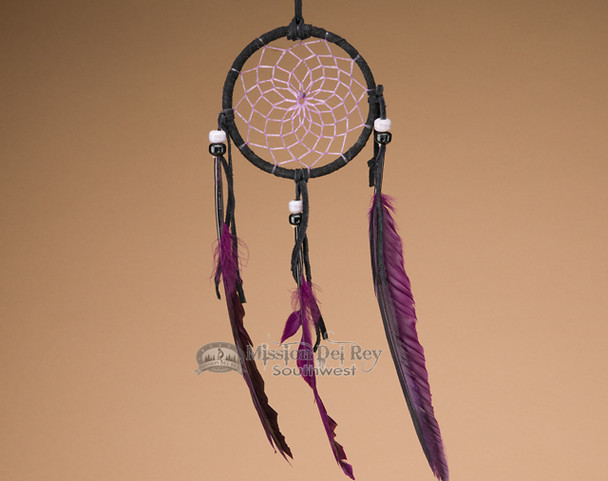 Native American dreamcatcher with purple web and feathers.
