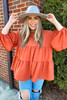 Model wearing the Tiered Babydoll Blouse in Rust from Dress Up Front View