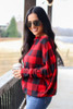 Model wearing the Red Buffalo Plaid Oversized Off the Shoulder Tunic with distressed jeans from Dress Up Side View