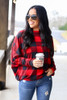 Model wearing the Red Buffalo Plaid Oversized Off the Shoulder Tunic with Starbucks Cup and high rise distressed skinny jeans from Dress Up Front View