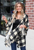 Model wearing the Buffalo Plaid Ruffle Sleeve Cardigan from Dress Up with a black tank