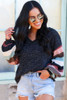 Model wearing the Black Statement Sleeve Brushed Knit Top with denim shorts and sunglasses Front View