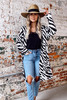 Model wearing the Zebra Longline Luxe Knit Cardigan with a wide brim hat