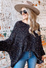 Model wearing the Chenille Confetti Knit Oversized Top in Black with high rise jeans, wide brim fedora hat and sunglasses