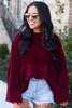 Model wearing the Velour Knit Oversized Babydoll Top in Burgundy with denim shorts from DressUp