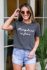 Model wearing the Kindness is Free Graphic Tee with light wash distressed denim shorts