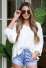 Model wearing the Balloon Sleeve Babydoll Blouse with light wash distressed denim shorts and aviator sunglasses
