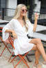 Model wearing the Gathered Sleeve Swiss Dot Romper Sitting View