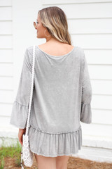 Model wearing Grey Ruffle Sleeve Acid Wash Top Back View