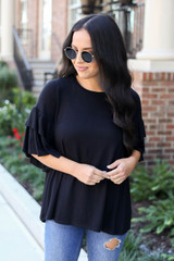 Black - Model wearing the Neely Tiered Sleeve Top in black- front detailed view