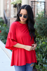 Model wearing the Neely Tiered Sleeve Top in red- front angle view
