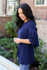 Model wearing the Neely Tiered Sleeve Top in navy- side view