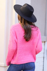 Model wearing the Fuzzy Knit Sweater from Dress Up in Neon Pink with High Rise Jeans Back View