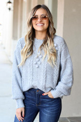 Model wearing the Cable Knit Pom Pom Sweater with jeans and sunglasses Front View
