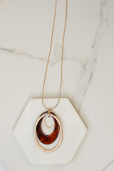Flat Lay of the Acrylic Oval Pendant Necklace in Rust from Dress Up