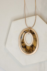 Flat Lay of the Acrylic Oval Pendant Necklace in Taupe from Dress Up