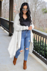 Model wearing the Popcorn Eyelash Knit Cardigan with distressed jeans and black tank and camel booties Front View