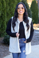 Model wearing the Chevron Faux Fur Vest with black long sleeve top and high rise jeans Front View