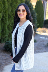Model wearing the Chevron Faux Fur Vest with black long sleeve top and high rise jeans Side View