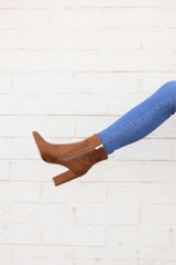 Model holding one leg up wearing the Block Heel Ankle Booties in Camel
