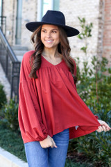 Model wearing the Balloon Sleeve Babydoll Top in Marsala with high rise jeans