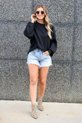 Model wearing the Ribbed Knit Oversized Top in Black with denim shorts and ankle booties