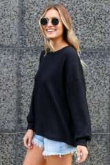 Model wearing the Ribbed Knit Oversized Top in Black Side View
