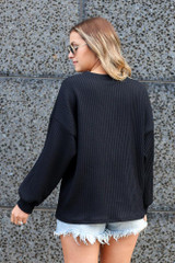 Model wearing the Ribbed Knit Oversized Top in Black Back View