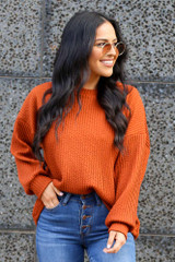 Model wearing the Ribbed Knit Oversized Top in Rust with high rise jeans