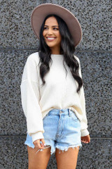 Model wearing the Ribbed Knit Oversized Top in Ivory with high rise denim shorts and wide brim fedora
