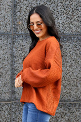 Model wearing the Ribbed Knit Oversized Top in Rust with high rise jeans Side View