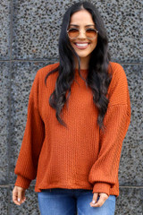 Model wearing the Ribbed Knit Oversized Top in Rust with high rise jeans Front View