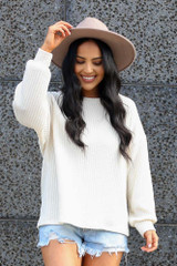 Model wearing the Ribbed Knit Oversized Top in Ivory with wide brim fedora Front View