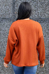 Model wearing the Ribbed Knit Oversized Top in Rust with high rise jeans Back View