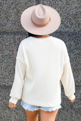 Model wearing the Ribbed Knit Oversized Top in Ivory with high rise denim shorts and wide brim fedora Back View