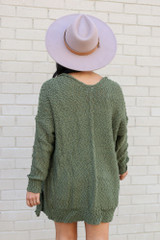Model wearing the Popcorn Knit Sweater Cardigan in Olive from Dress Up Back View