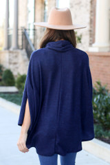 Model wearing the Brushed Knit Cowl Neck Oversized Poncho in Navy with medium wash jeans and wide brim fedora from Dress Up Back View