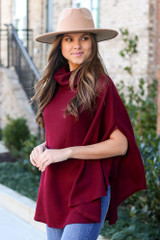 Model wearing the Brushed Knit Cowl Neck Oversized Poncho in Burgundy with medium wash jeans from Dress Up Side View. Wide Brim Fedora Hat in tan.
