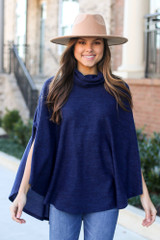 Model wearing the Brushed Knit Cowl Neck Oversized Poncho in Navy with medium wash jeans and wide brim fedora from Dress Up Front View