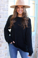 Model wearing the Popcorn Knit Oversized Top in Black with high rise skinny jeans from Dress Up Boutique Front View