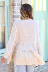 Model wearing the Ivory Tiered Babydoll Tunic with high rise jeans from Dress Up Back view