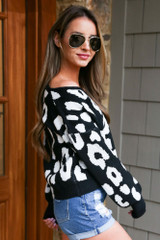Model wearing the Black Leopard Cropped Luxe Knit Top with denim shorts and wide brim fedora hat from Dress Up Side View