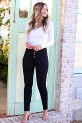 Model wearing the High-Rise Skinny Jeans in Black with a white long sleeve crop top